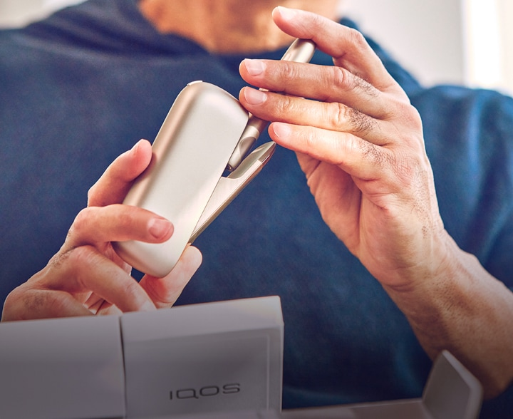 A person wearing blue holding a gold IQOS device.